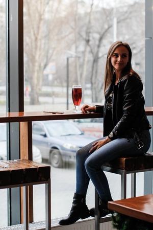 Eine junge schöne Frau sitzt auf einem Barhocker an einem großen Fenster und wartet auf das Mittagessen Standard-Bild
