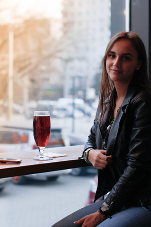 A young beautiful woman is sitting on a bar stool by a large window waiting for lunch Stock Photo