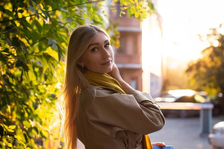 Portrait of a beautiful young woman who enjoys autumn while walking around the city. Attractive blonde in a raincoat and a yellow scarf on a background of autumn trees
