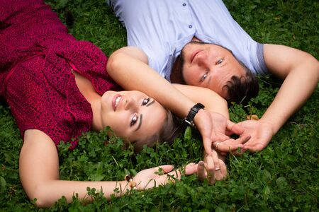 Happy couple resting in a park on green grass. Slow Motion. Smiling man and woman talking, enjoying a warm summer day. Joyful family. Young lovers lying on the lawn, resting outdoors