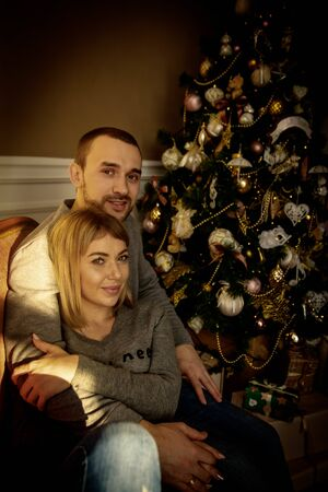 Loving young couple spends Christmas at home near a decorated, festive Christmas tree. Man and woman are happy spending time together.