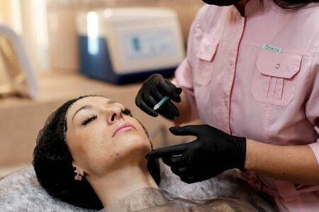 Russia, Novosibirsk, January 5, 2020. Woman lies with her eyes closed during the procedure in the beauty parlor
