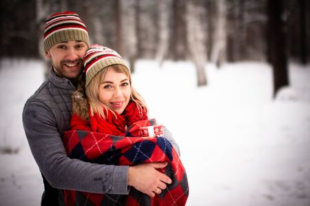 Boys and girls in love have fun and play with snow in the winter forest. Happiness and smiles on the faces of a young couple in love.
