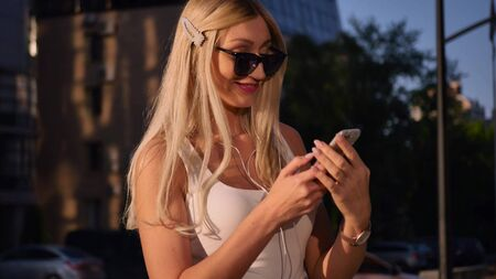 Attractive young woman listening to music in headphone use smartphone at city walk sunset look around smile portrait close up.