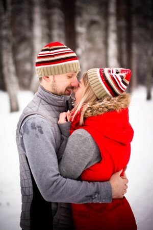 Boys and girls in love have fun and play with snow in the winter forest. Happiness and smiles on the faces of a young couple in love