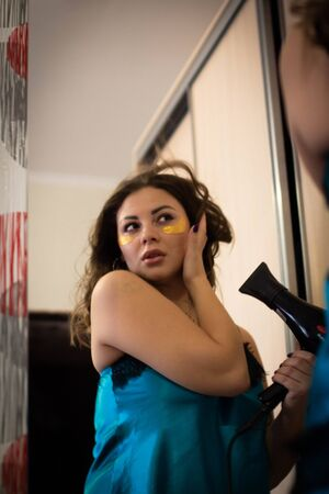 Attractive woman singing in a hairdryer. Portrait of a woman singing at home with a hairdryer. Beautiful model have fun in the wardrobe at morning. Emotional woman singing at home.