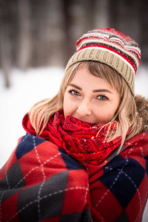 Portrait of an attractive young woman outdoors in a winter park. Snowy forest.