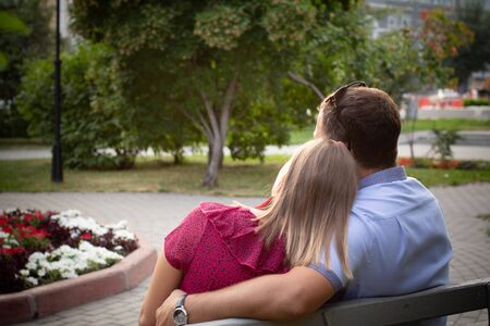 couple in love is sitting on a bench. Man and woman enjoy each others conversation in the summer park