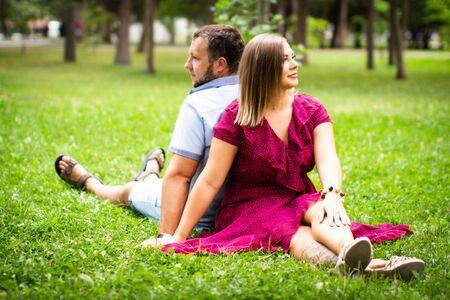 Couple heureux se reposant dans un parc sur l'herbe verte. Ralenti. Homme et femme souriants parlant tout en profitant d'une chaude journée d'été. Famille joyeuse. Les jeunes amoureux s'assoient sur une pelouse dans un parc, se reposant à l'extérieur.