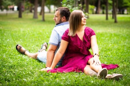 Happy couple resting in a park on green grass. Slow motion. Smiling man and woman talking while enjoying a warm summer day. Joyful family. Young lovers sit on a lawn in a park, resting outdoors.