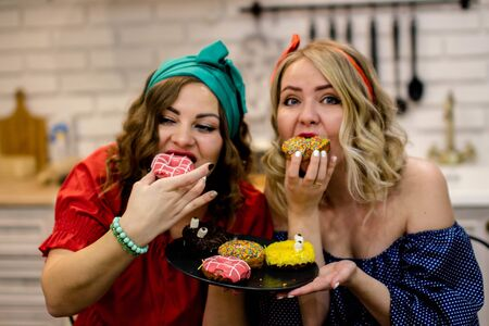 Two women bite tasty donuts during a diet. 版權商用圖片