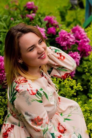 portrait of a beautiful young woman with peonies flowers outdoors. 版權商用圖片