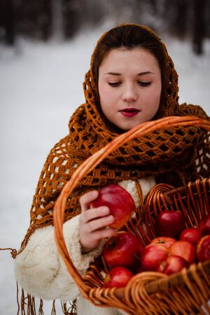 young woman in traditional Russian clothes with a basket of apples in her hands in the winter forest. 版權商用圖片