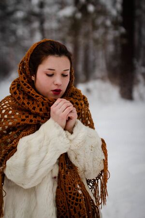 Portrait of a young woman outdoors who is breathing in her arms to keep warm while walking in the winter park 版權商用圖片