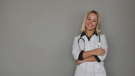 female doctor in a white medical coat on a gray background. healthcare concept