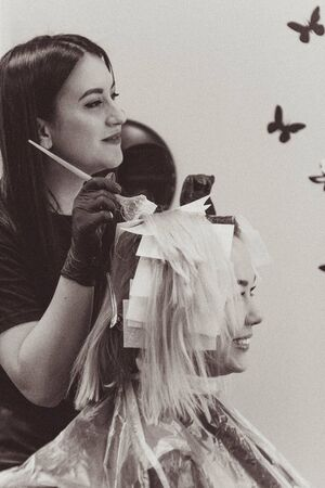 Beautiful young woman hairdresser giving new haircut to female client at salon Banque d'images