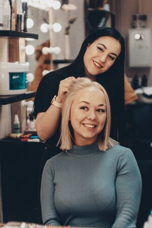 Beautiful young woman hairdresser giving new haircut to female client at salon
