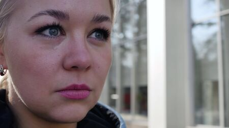 Portrait of a crying blonde 4k. Tears roll down the face of a young woman. A sad woman wipes her face, eyes full of tears.