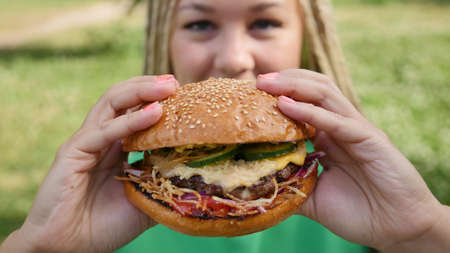 Pretty young woman is eating appetizing hamburger on the street. Close-up Zdjęcie Seryjne