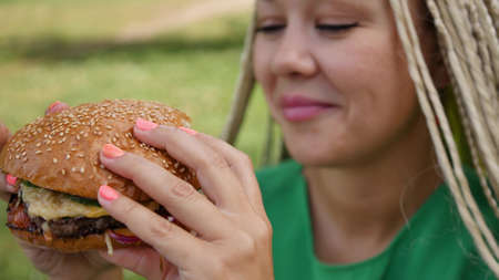 Pretty young woman is eating appetizing hamburger on the street. Close-up Archivio Fotografico