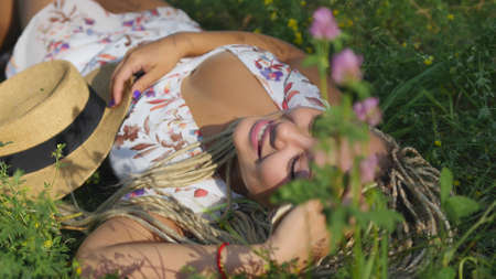 Attractive young woman lying on grass, smiling