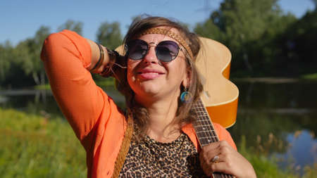 nature, summer vacation, vacation and people concept - happy smiling woman in sunglasses stands with a guitar on her shoulder.