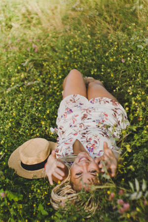 Attractive young smiling woman lying on green grass in park