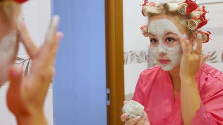 Beautiful young woman looks in the mirror and applies a cosmetic face mask. A pretty blonde in curlers on her head is getting ready for a party