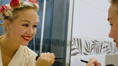 A beautiful young woman looks in the mirror and applies powder to her face. Cute blonde in curlers on her head getting ready for a party