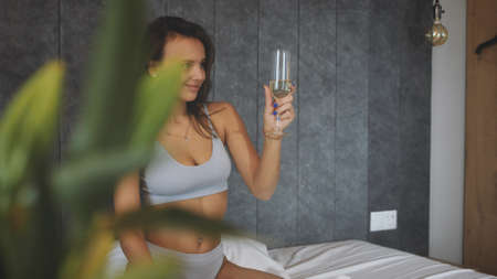 Attractive woman sitting on bed in hotel with glass of sparkling wine Фото со стока