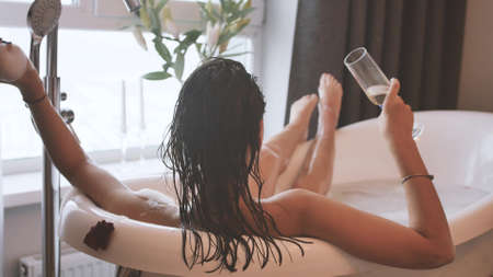 Relaxed woman drinking champagne in a luxurious bath