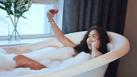 Attractive young woman takes a bubble bath and talks on a smartphone. Relaxation and leisure concept.