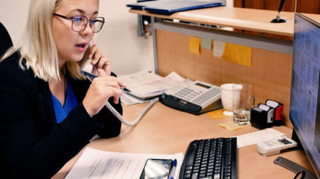 Smiling young business woman talking on the phone. Pretty blonde works in the office.