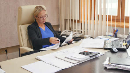 A young business woman is working in her office. Blonde at her desk in the office.