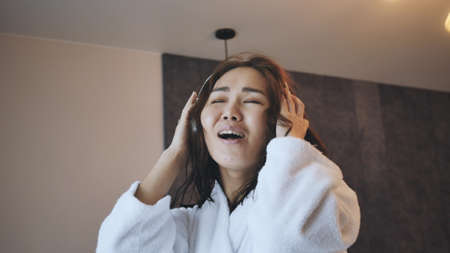 beautiful asian woman in white robe listens to music with wireless headphones in the bathroom.