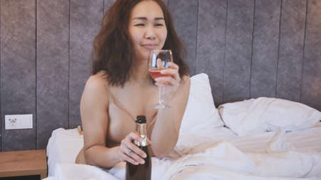 Attractive asian woman drinking champagne while sitting on bed in hotel.