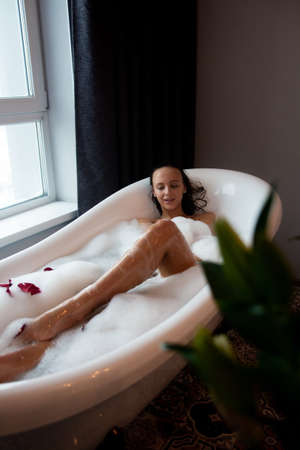 Young beautiful woman relaxing while listening to music in wireless headphones in bubble bath.