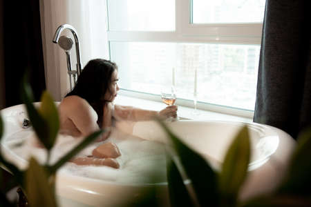 Relaxed asian woman drinking champagne in a luxurious bath Фото со стока