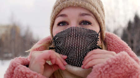 A woman in a coral black mask and a fur hat on a city street in a cold winter.
