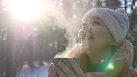 Attractive young beautiful woman walks in the winter snowy forest and drinks hot tea, coffee from a mug. Portrait of a happy girl in the winter forest. Lifestyle, happiness, vacation concept 版權商用圖片