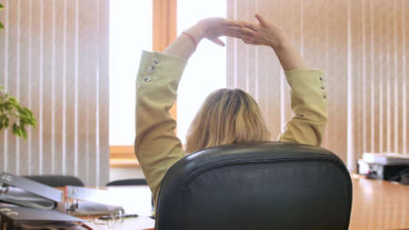 Business woman in the office. Confident business woman relaxing on a chair in her office.