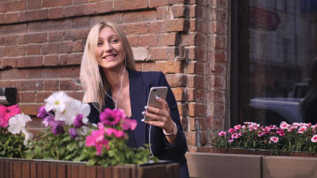 Young business woman in a suit speaks by video calling on her smartphone. Beautiful blonde resting on a bench during the lunch break