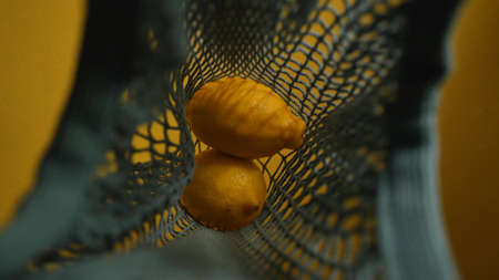close-up of lemons on a string bag on a yellow background Stock fotó