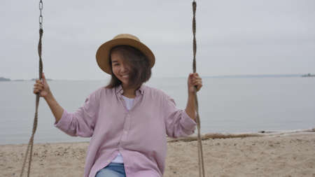 Young relaxing asian woman enjoying the feeling of freedom and fresh air, swinging on a swing near the sea beach. A serene summer getaway in a beautiful outdoor resort