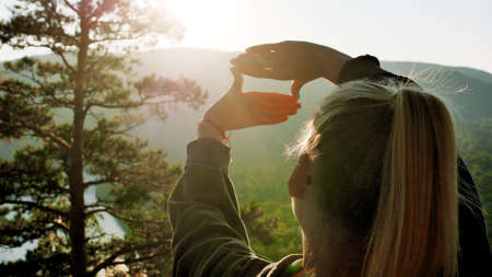 A woman traveler stands on the top of a mountain near the banks of the Mana River in Siberia and enjoys a beautiful view.