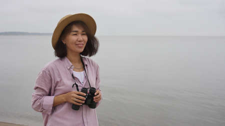 Beautiful asian woman in a hat stands on the seashore and looks through binoculars and enjoys a beautiful day