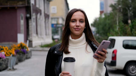 Happy caucasian business woman in white sweater and black leather jacket walking down the street to her company office holding coffee and smartphone. Stock fotó