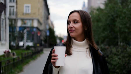 Happy caucasian business woman in a white sweater and black leather jacket walks down the street to her company office holding coffee in her hands