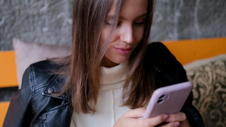 A beautiful woman sits in a cafe and looks into her smartphone. Casual lifestyle portrait. Business lady
