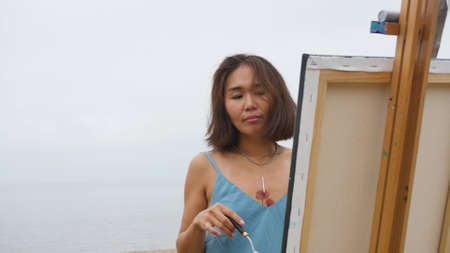 Beautiful asian woman in a blue dress paints a picture on the sea mebegu on a cloudy day
